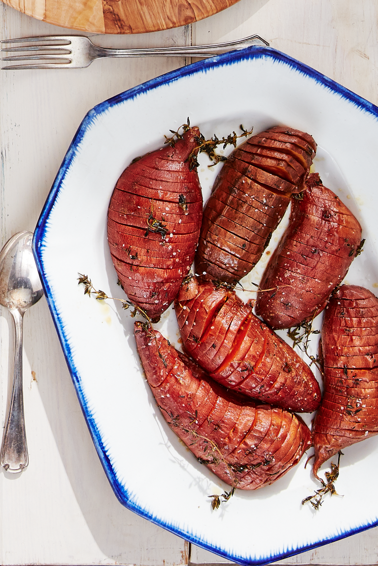 """<p>Maple syrup and fragrant thyme round out this sweet-and-savory dish. It's a fall masterpiece!</p><p><strong><a href=""""https://www.countryliving.com/food-drinks/a28942812/roasted-hasselback-sweet-potatoes-recipe/"""" rel=""""nofollow noopener"""" target=""""_blank"""" data-ylk=""""slk:Get the recipe"""" class=""""link rapid-noclick-resp"""">Get the recipe</a>.</strong></p><p><a class=""""link rapid-noclick-resp"""" href=""""https://www.amazon.com/Nordic-Ware-Natural-Aluminum-Commercial/dp/B0049C2S32/?tag=syn-yahoo-20&ascsubtag=%5Bartid%7C10050.g.877%5Bsrc%7Cyahoo-us"""" rel=""""nofollow noopener"""" target=""""_blank"""" data-ylk=""""slk:SHOP BAKING SHEETS"""">SHOP BAKING SHEETS</a></p>"""