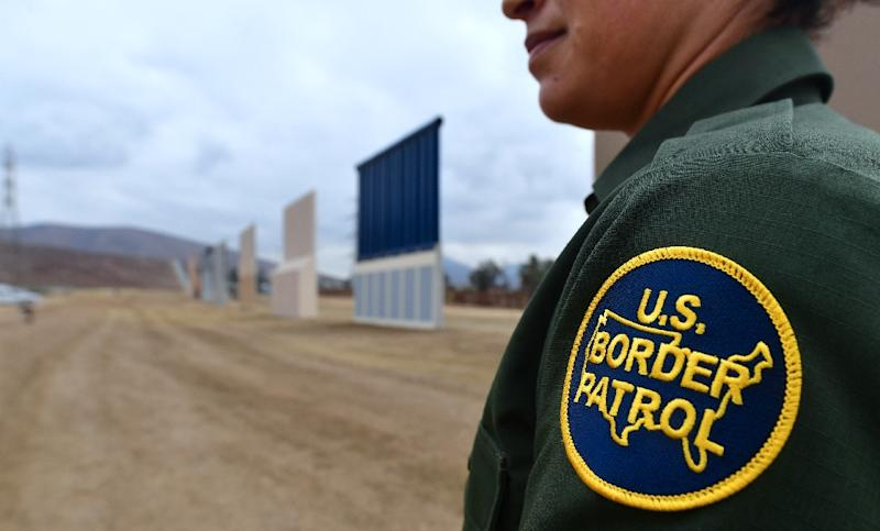 A US Border Patrol agent stands guard in San Diego, California near prototypes of President Donald Trump's proposed border wall