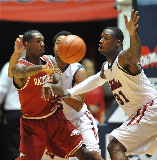 Arkansas' Mardracus Wade (1) passes around Mississippi's Murphy Holloway (31) and Jelan Kendrick (45) during an NCAA college basketball game in Oxford, Miss., Wednesday, Jan. 11, 2012. (AP Photo/Oxford Eagle, Bruce Newman) MAGS OUT, NO SALES, MANDATORY CREDIT