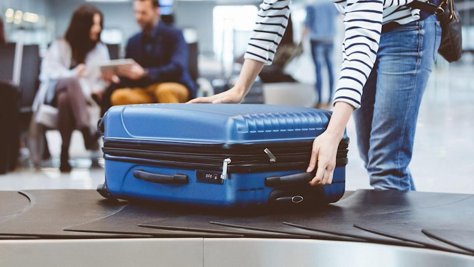 Young woman passenger collecting her luggage from conveyor belt.