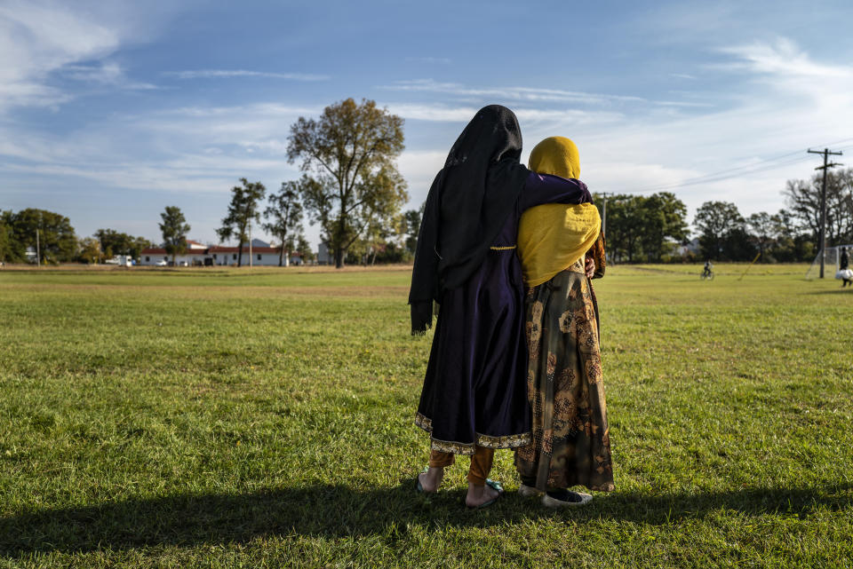 Afghan refugee girls watch a soccer game from a distance near the Village at the Ft. McCoy U.S. Army base on Thursday, Sept. 30, 2021 in Ft. McCoy, Wis. The fort is one of eight military installations across the country that are temporarily housing the tens of thousands of Afghans who were forced to flee their homeland in August after the U.S. withdrew its forces from Afghanistan and the Taliban took control. (Barbara Davidson/Pool Photo via AP)