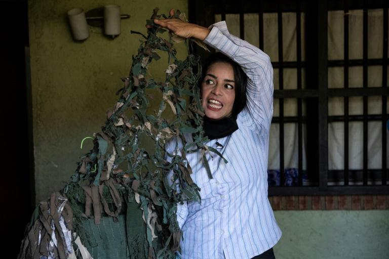 Ismaira Figueroa, a sniper for the Bolivarian militia, shows the camouflage suit that she made for herself with clothes of fallen comrades, at her house in Baruta neighbourhood of Caracas