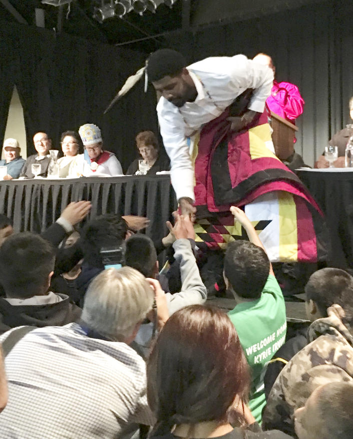 Boston Celtics basketball star Kyrie Irving accepts gifts from students on the Standing Rock Indian Reservation in North Dakota on Thursday, Aug 23, 2018. Irving traveled to the reservation from which his mother came to be honored by the tribe for his heritage and his support of its battle against the Dakota Access oil pipeline. (AP Photo/Blake Nicholson)