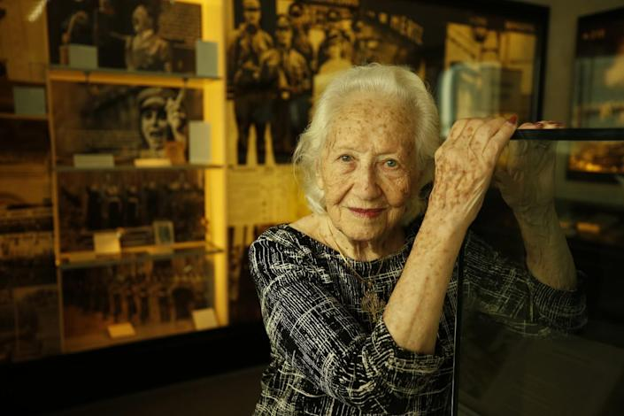 A woman poses with her hands atop a glass display case. Behind her, historical images and artifacts are on display.