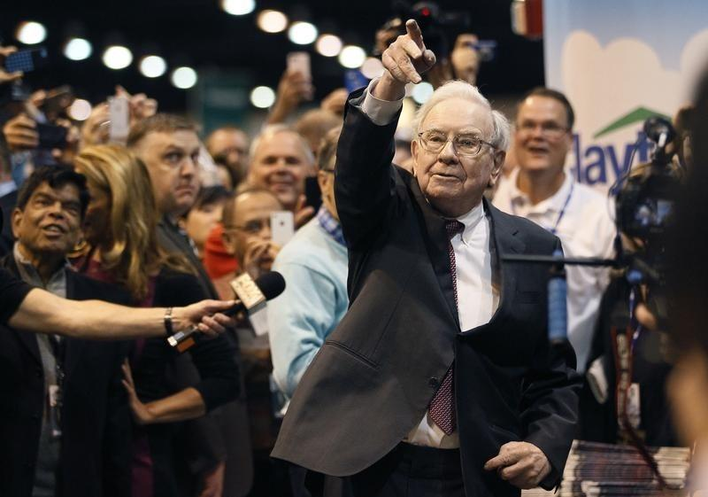 Berkshire Hathaway CEO Buffett points after throwing a newspaper during a competition at a trade show, at the company's annual meeting in Omaha
