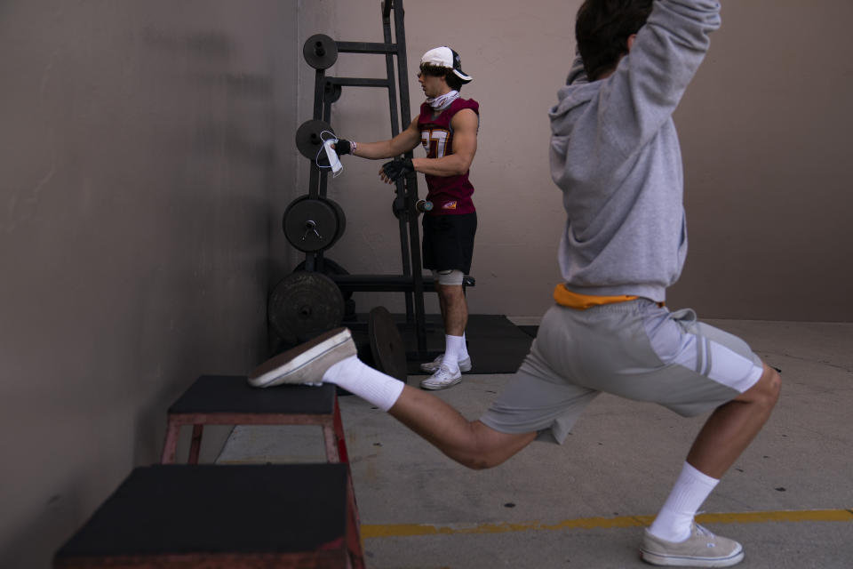 El Modena tight end Owen Mull hangs his mask on a weight bar while working out at a school gym temporarily set up at outdoor racquetball courts before the team's high school football game with El Dorado in Orange, Calif., Friday, March 19, 2021. (AP Photo/Jae C. Hong)