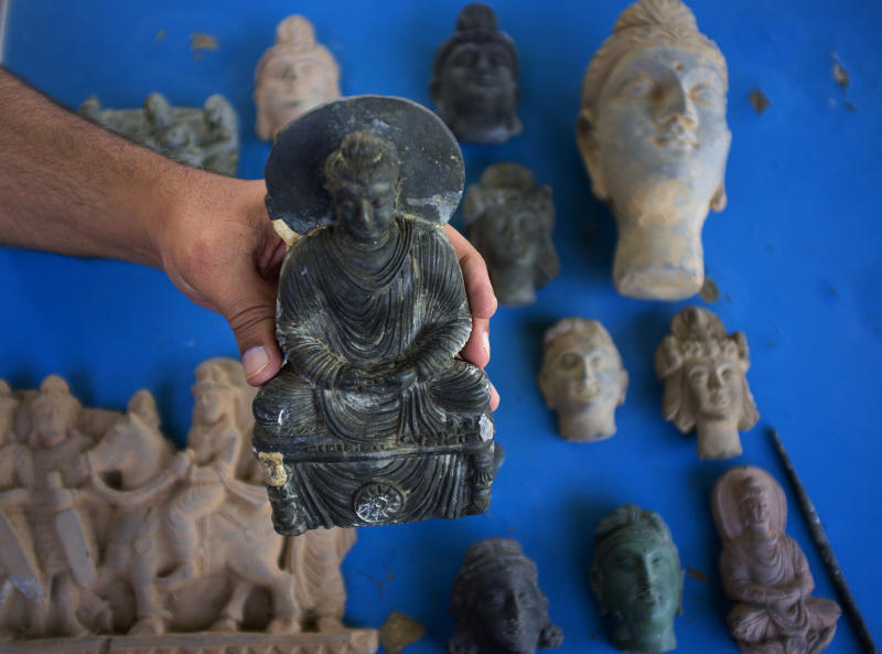 In this photo taken on July 17, 2012, A Pakistani artist Salahud Deen shows samples of Buddhist artifacts he created in Taxila, a famous Buddhist archeologist site near Islamabad, Pakistan. Lacking the necessary cash and manpower, Pakistan is struggling to stem the flow of millions of dollars in ancient Buddhist artifacts that shadowy criminal gangs dig up from the country's northwest and smuggle to collectors around the world. (AP Photo/B.K. Bangash)