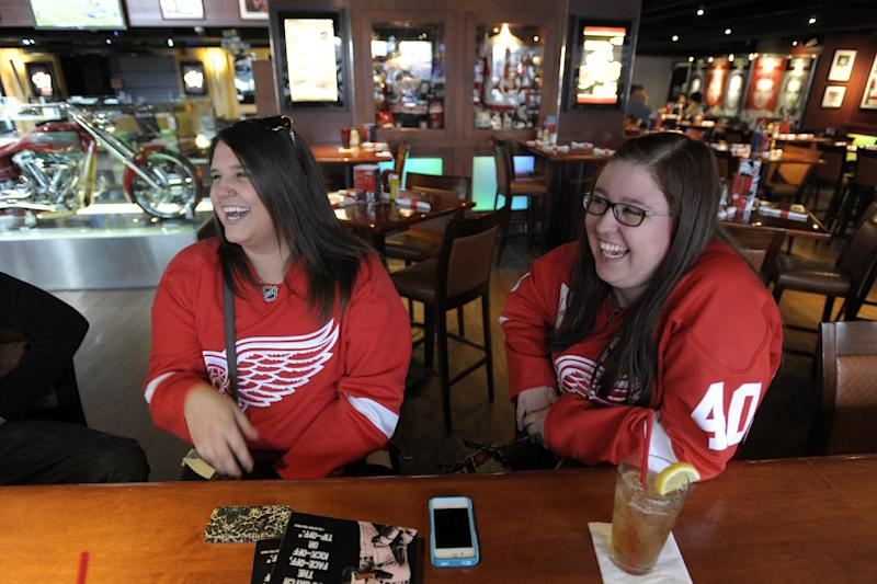 Detroit  Red Wings fans Katie Miller, left, of Toledo, Ohio, and Emily Radwanski, of Roseville, Mich., wear their Red Wings jerseys while hanging out at the Hockeytown Cafe in Detroit, Sunday, Jan. 6, 2013. With the season on the line, the NHL and the players' association agreed on a tentative pact to end a 113-day lockout and save what was left of a fractured hockey schedule. (AP Photo/The Detroit News, David Guralnick) DETROIT FREE PRESS OUT; HUFFINGTON POST OUT.