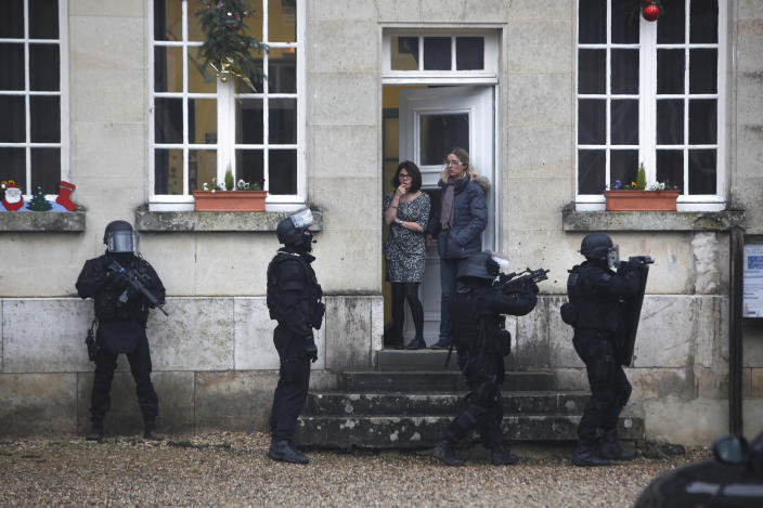 FILE - In this Jan. 8, 2015 file photo, French riot officers patrol in Longpont, north of Paris, France. The January 2015 attacks against Charlie Hebdo and, two days later, a kosher supermarket, touched off a wave of killings claimed by the Islamic State group across Europe. Seventeen people died along with the three attackers. Thirteen men and a woman accused of providing the attackers with weapons and logistics go on trial on terrorism charges Wednesday Sept. 2, 2020. (AP Photo/Thibault Camus, File)