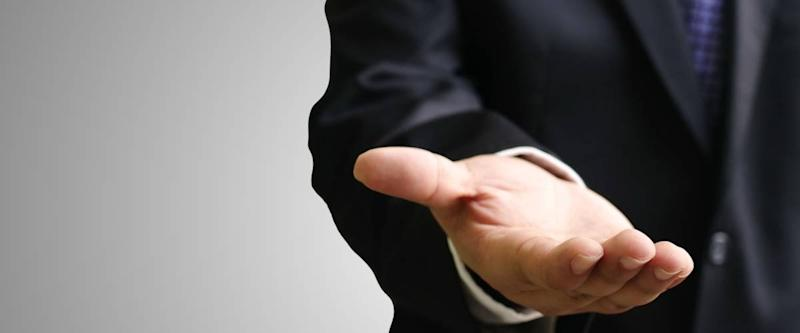 Businessman in a suit with his hand out for money
