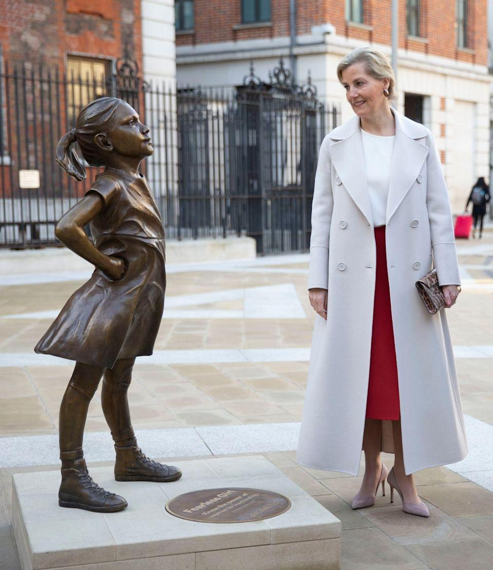 """<p>Sophie looked chic in a white blouse, red Valentino skirt, and grey double-breasted coat by <a href=""""https://www.net-a-porter.com/us/en/Shop/Designers/Max_Mara/Clothing?gclsrc=aw.ds&cm_mmc=GoogleUS--c-_-NAP_EN_NY-_-NAP+-+AM+-+NY+-+Designer_Max+Mara+-+BT--Max+Mara+-+Clothing+-+Coats-_-max%20mara%20coats_e_aud-342581009201:kwd-662289229_AM&gclid=CjwKCAiAwojkBRBbEiwAeRcJZCLFcHWWrcEyMoWM4Os33y20C7KfzwK3DgLP7XZPyhd90WCu8kTriBoCARkQAvD_BwE&pn=1&npp=60&image_view=product&dScroll=0"""" rel=""""nofollow noopener"""" target=""""_blank"""" data-ylk=""""slk:Max Mara"""" class=""""link rapid-noclick-resp"""">Max Mara</a> as she <a href=""""https://www.townandcountrymag.com/society/tradition/a26762582/sophie-countess-of-wessex-fearless-girl-statue-london-stock-exchange/"""" rel=""""nofollow noopener"""" target=""""_blank"""" data-ylk=""""slk:visited the new &quot;Fearless Girl&quot; outside of the London Stock Exchange"""" class=""""link rapid-noclick-resp"""">visited the new """"Fearless Girl"""" outside of the London Stock Exchange</a> for International Women's Day. The Countess paired the look with a snakeskin clutch, brown pear-shaped earrings, and nude suede heels. </p>"""