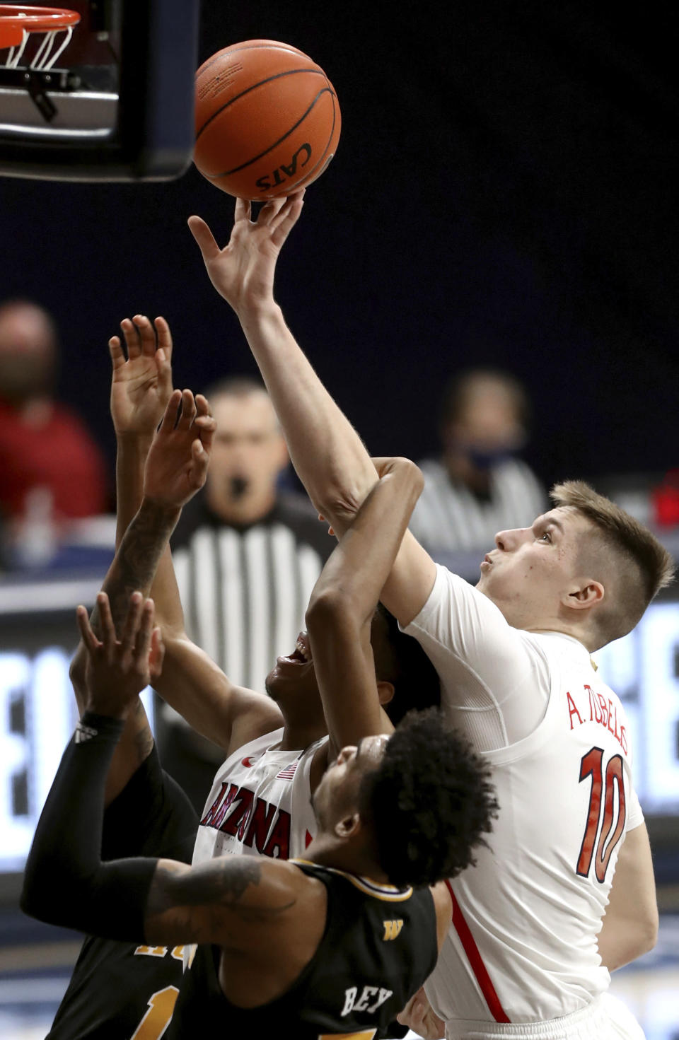 Arizona forward Azuolas Tubelis (10, right, gets tangled with teammate guard Dalen Terry (4) in front of Washington guard Jamal Bey (5) while trying to drag down a rebound in the first half of an NCAA college basketball game Saturday, Feb. 27, 2021, in Tucson, Ariz. (Kelly Presnell/Arizona Daily Star via AP)