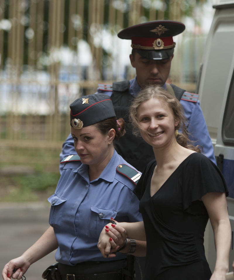 "Maria Alekhina, foreground right, a member of feminist punk group Pussy Riot is escorted to a court room in Moscow, Russia, Tuesday, Aug. 7, 2012. Russia's President Vladimir Putin on Thursday criticized the feminist punk rockers facing trial for performing a ""punk prayer"" against him at Moscow's main cathedral, but said that a punishment for them shouldn't be too severe. (AP Photo/Alexander Zemlianichenko)"