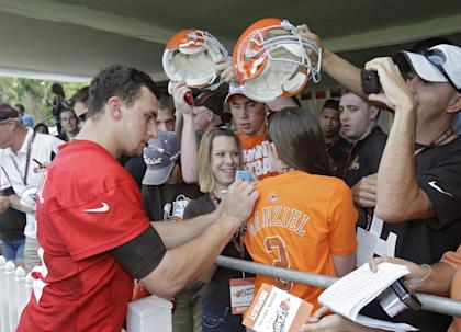 Signing autographs isn't a big deal anymore for Johnny Manziel. (AP)