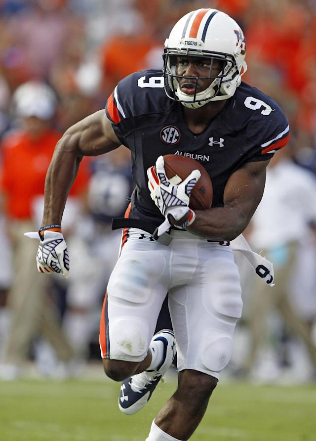 Auburn defensive back Jermaine Whitehead (9) intercepts a pass and returns it for a touchdown against Arkansas during the second half of an NCAA college football game on Saturday, Aug. 30, 2014, in Auburn, Ala. (AP Photo/Butch Dill)
