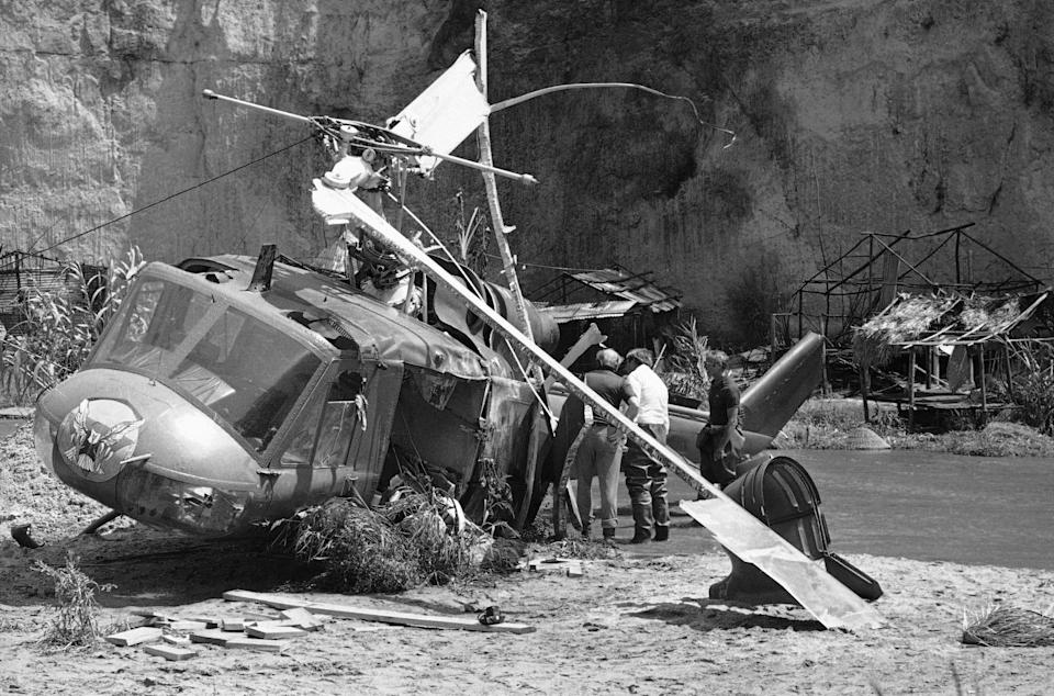 """Investigators look over wreckage of helicopter which crashed during filming of a movie in a private park near Castaic, California on Friday, July 23, 1982. The crash killed veteran actor Vic Morrow and two child actors during filming of scene in a movie revival of """"The Twilight Zone."""" (AP Photo/Scott Harms)"""