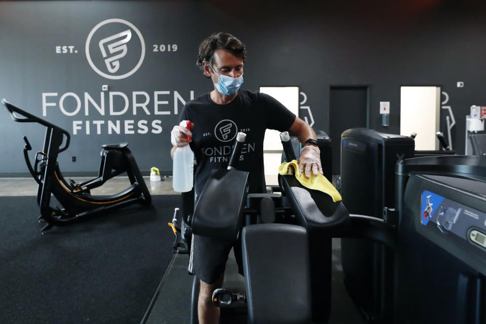 FILE - In this May 14, 2020 file photo, Terry Sullivan, general manager of Fondren Fitness, a Jackson, Miss., fitness center, sanitizes a workout machine. Fitness regimens shifted from the gym to the home in a big way during 2020. Interactive fitness bike maker Peloton was one of the biggest winners of the workout-from-home trend as gyms did not fare so well as people avoided crowded places. (AP Photo/Rogelio V. Solis)