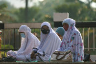 Muslim women wearing protective masks wait to pray outside the National Mosque while celebrating Eid al-Fitr, the Muslim festival marking the end the holy fasting month of Ramadan in Kuala Lumpur, Malaysia, Thursday, May 13, 2021. (AP Photo/Vincent Thian)