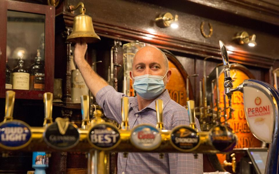 General manager Michael Rogerson rings for last orders in the Horseshoe Bar in Glasgow - Robert Perry/Shutterstock