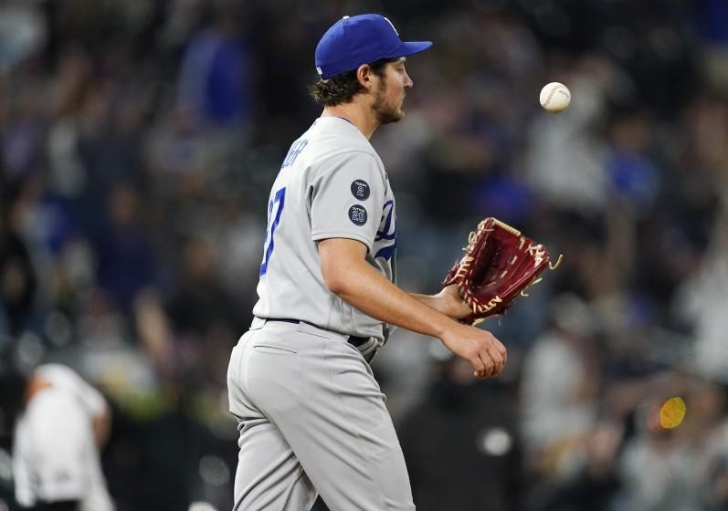 Los Angeles Dodgers starting pitcher Trevor Bauer tosses a new ball after giving up a two-run home run to Colorado Rockies' Ryan McMahon in the seventh inning of a baseball game Friday, April 2, 2021, in Denver. (AP Photo/David Zalubowski)