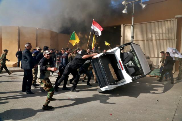 Protesters turn over a vehicle inside the U.S. Embassy compound in Baghdad on Dec 31. (Photo: Khalid Mohammed/AP)