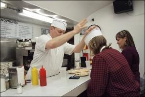 Short order cook giving someone a hat