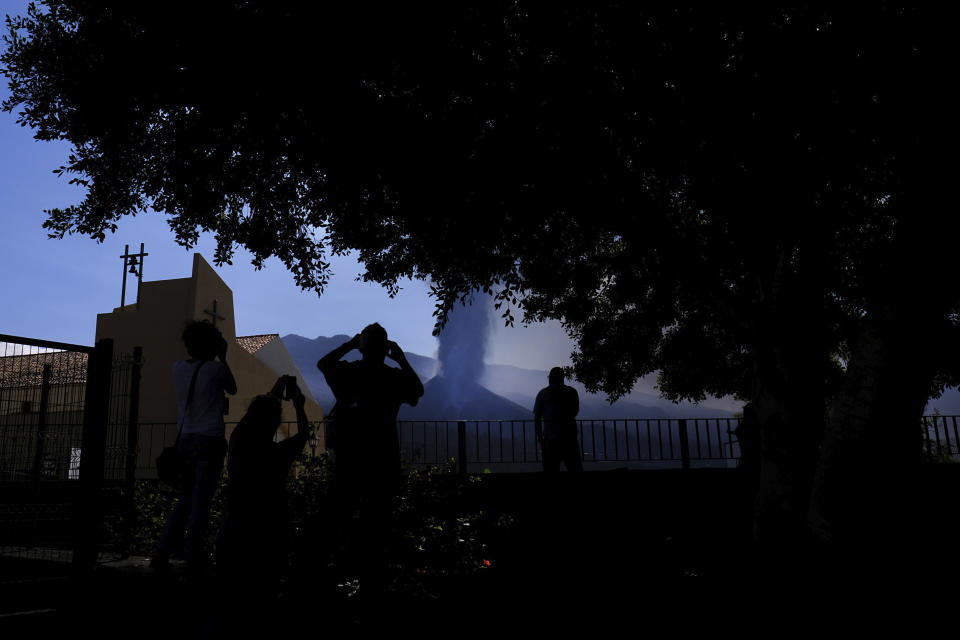 People look towards a volcano as it continues to erupt in El Paso on the canary island of La Palma, Spain, Saturday Oct. 9, 2021. A new lava flow has belched out from the La Palma volcano and it threatens to spread more destruction on the Atlantic Ocean island where molten rock streams have already engulfed over 1,000 buildings. The partial collapse of the volcanic cone overnight sent a new lava stream Saturday heading toward the western shore of the island. (AP Photo/Daniel Roca)
