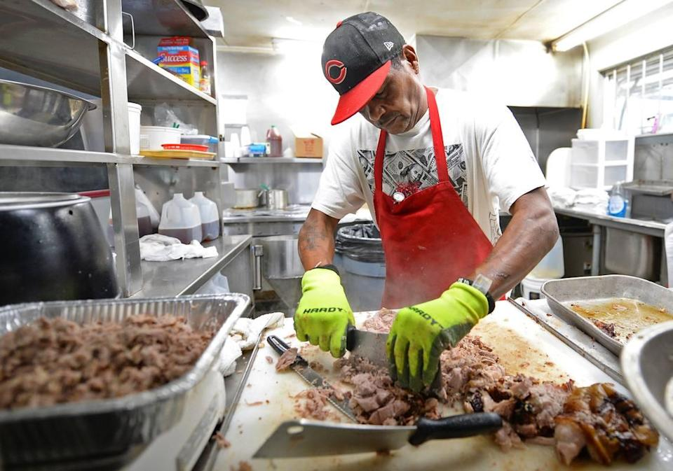 Meat cutter Charles Spikes chops up a pork shoulder at Bridges Barbecue Lodge in Shelby, NC in time for the lunch crowd on Wednesday, September 1, 2021.