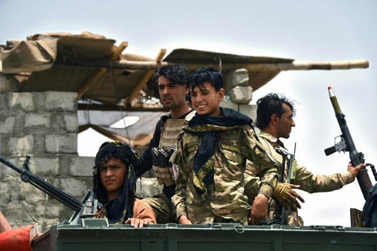 Afghan policemen sit on an armored vehicle at a checkpoint in Panjwai district of Kandahar province