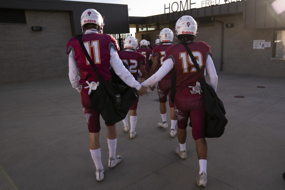 El Modena players hold hands as they walk into a stadium for the team's high school football game with El Dorado in Orange, Calif., Friday, March 19, 2021. (AP Photo/Jae C. Hong)