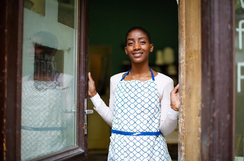 African woman standing at a ceramic pottery studio door. Happy pottery studio owner standing at the entrance door.