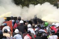Tear gas and fire extinguisher gas float around demonstrators during a protest against the military coup in Naypyitaw