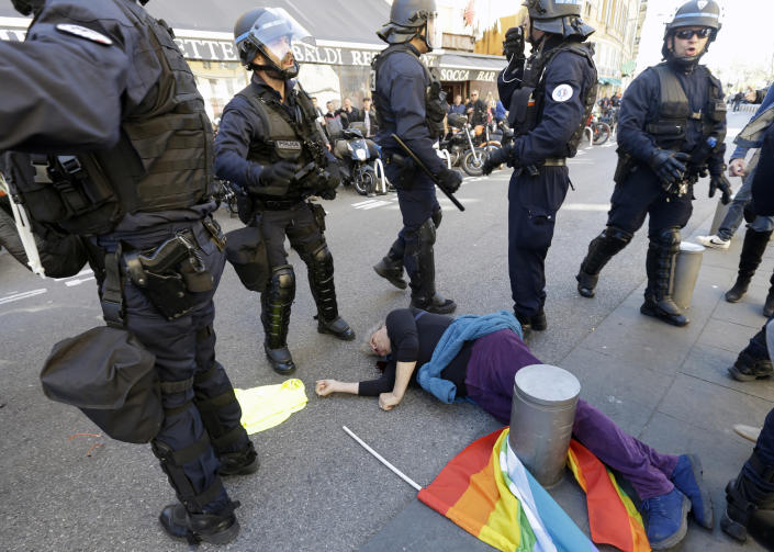 FILE - In this March 23, 2019 file picture, anti-globalization activist Genevieve Legay, 73, lies unconscious after collapsing on the ground during a protest in Nice, southeastern France, as part of the 19th round of the yellow vests movement. As videos helped reveal many cases of police brutality, French civil rights activists voiced fears that a new security law would threaten efforts by people from minorities and poor neighborhoods to document incidents involving law enforcement officers. French President Emmanuel Macron's government is pushing a new security bill that would notably make it illegal to publish images of officers with intent to cause them harm.(AP Photo/Claude Paris, File)