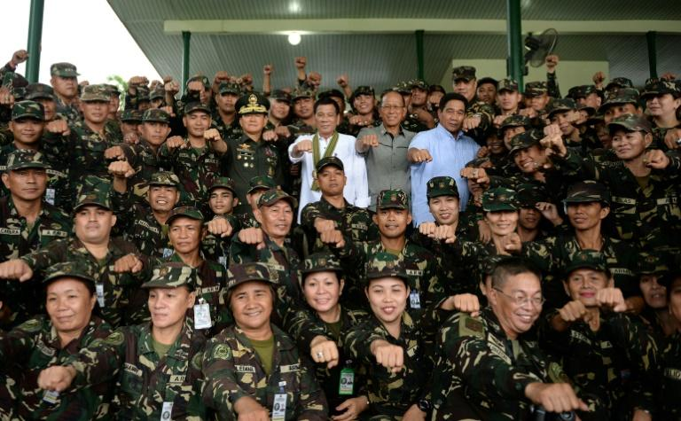"""Philippine President Rodrigo Duterte (C) gesturing with clenched fists for a photo session during a """"talk to the troops"""" visit to meet military personnel in Manila"""