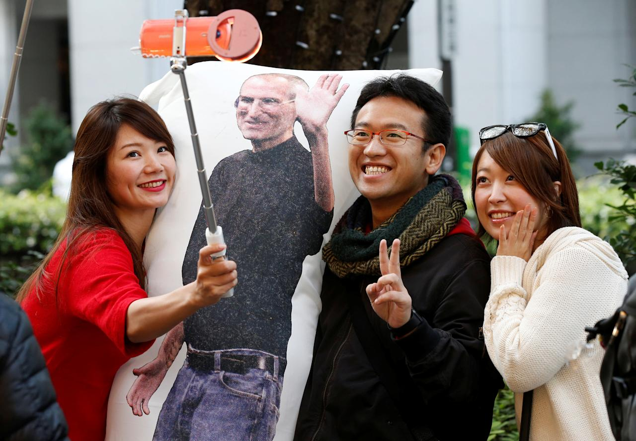 Ayano Tominaga (L) and other customers pose for a selfie photo with a cushion printed with a portrait of Apple co-founder Steve Jobs on it, as they wait in queue for the release of Apple's new iPhone X in front of the Apple Store in Tokyo's Omotesando shopping district, Japan, November 3, 2017.  REUTERS/Toru Hanai