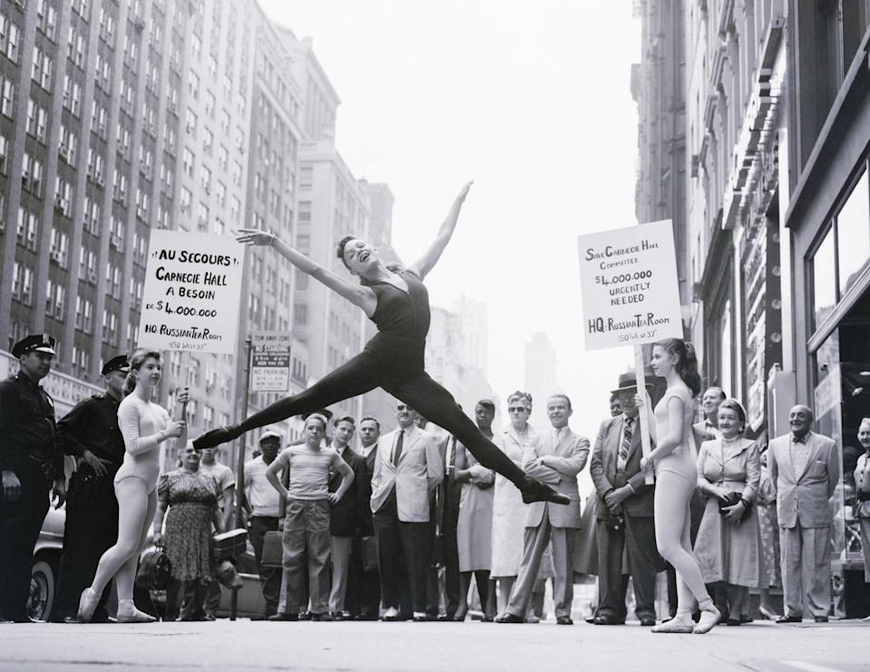 "Bystanders gather around to watch 15-year-old Valerie Harper, a ballet dancer from Jersey City, execute a flying split. Two other dancers, stationed on either side of her, hold picket signs as part of the campaign to ""save Carnegie Hall"" from being sold to a hotel builder."