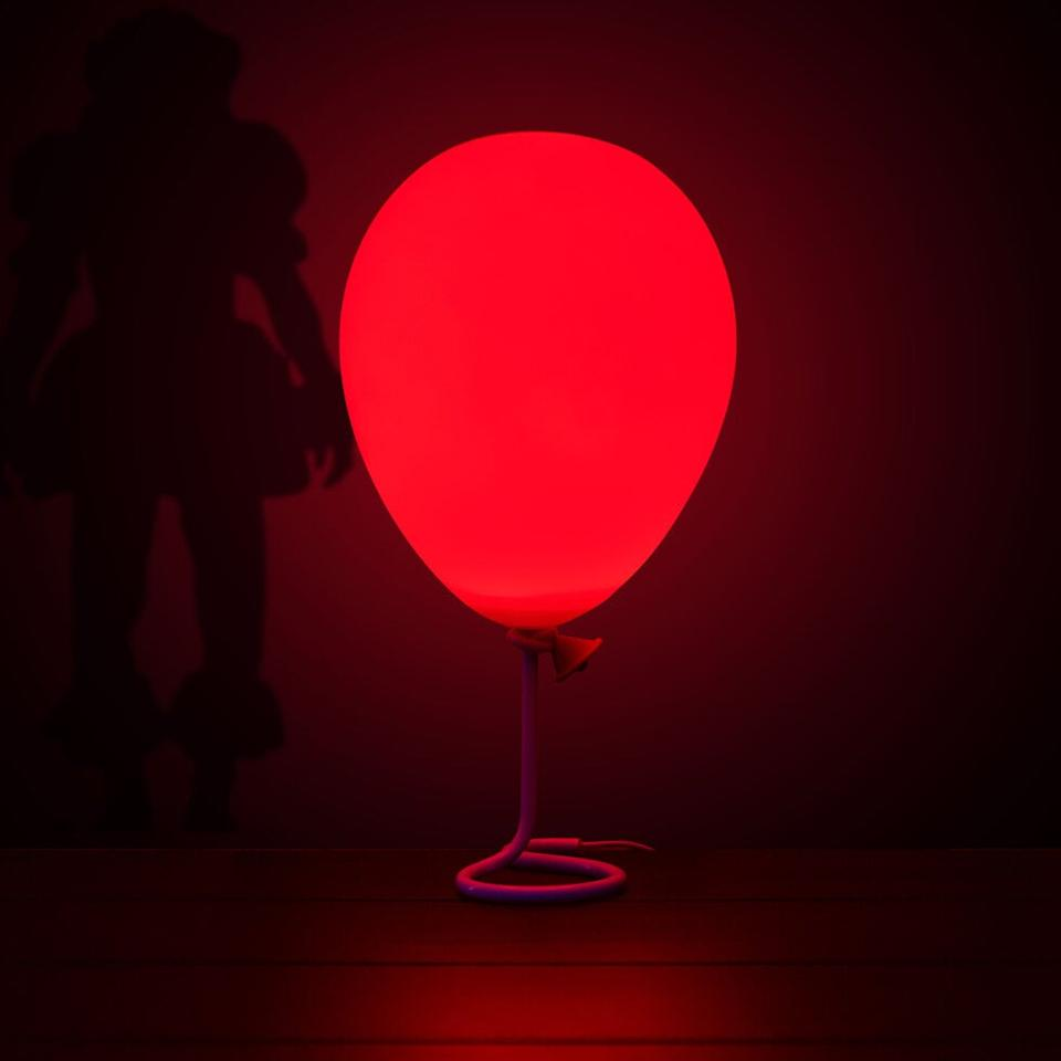"""<p>With its red glow, the <a href=""""https://www.popsugar.com/buy/Pennywise-Balloon-Lamp-487702?p_name=Pennywise%20Balloon%20Lamp&retailer=firebox.com&pid=487702&price=37&evar1=casa%3Aus&evar9=46578659&evar98=https%3A%2F%2Fwww.popsugar.com%2Fhome%2Fphoto-gallery%2F46578659%2Fimage%2F46578661%2FPennywise-Balloon-Lamp&list1=halloween%2Challoween%20decor%2Cit%20chapter%20two&prop13=api&pdata=1"""" rel=""""nofollow"""" data-shoppable-link=""""1"""" target=""""_blank"""" class=""""_e75a791d-denali-editor-page-rtfLink ga-track"""" data-ga-category=""""Related"""" data-ga-label=""""http://www.firebox.com/Pennywise-Balloon-Lamp/p9188?aff=512&amp;awc=550_1567639916_c800e6f8a662af9eda1ca83809e5fbd9&amp;utm_source=AffiliateWindow&amp;utm_medium=Affiliates&amp;utm_content=Skimlinks&amp;utm_campaign=Skimlinks&amp;ref=popsugar.com"""" data-ga-action=""""In-Line Links"""">Pennywise Balloon Lamp</a> ($37) works as a spooky nightlight or a fun <a class=""""sugar-inline-link ga-track"""" title=""""Latest photos and news for Halloween"""" href=""""https://www.popsugar.com/Halloween"""" target=""""_blank"""" data-ga-category=""""Related"""" data-ga-label=""""https://www.popsugar.com/Halloween"""" data-ga-action=""""&lt;-related-&gt; Links"""">Halloween</a> party centerpiece.</p>"""