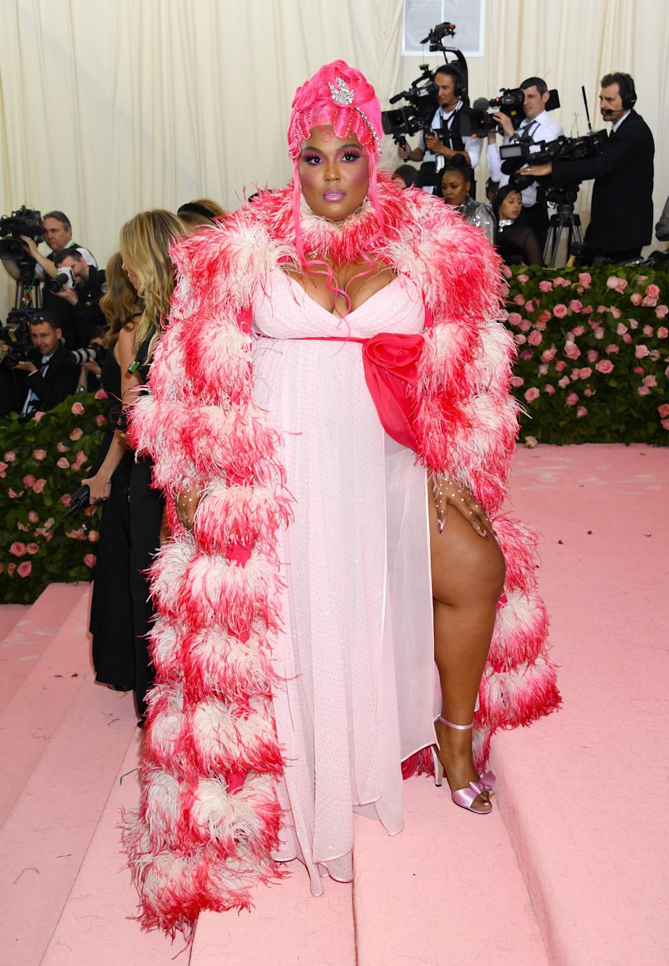 """Lizzo went all out for her first Met Gala. Keeping to the theme of """"Camp,"""" she dyed her pink and wore a custom Marc Jacobs gown and the most flamboyant feather boa we have ever seen."""