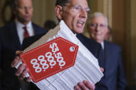 """Sen. John Barrasso, R-Wyo., center, flanked by Senate Minority Whip John Thune, R-S.D., left, and Senate Minority Leader Mitch McConnell, R-Ky., right, hoists a copy of the Democrats' $3.5 trillion """"Build Back Better"""" package as they speak to reporters after a Republican policy meeting, at the Capitol in Washington, Tuesday, Sept. 28, 2021. (AP Photo/J. Scott Applewhite)"""