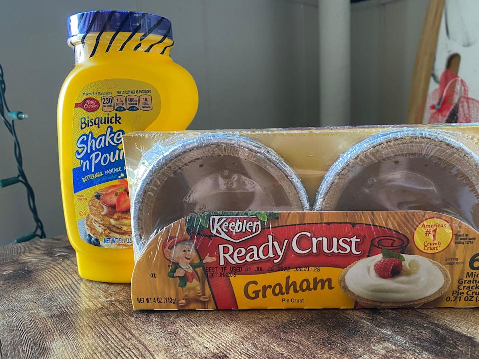 The Shake 'n Pour yellow bottle next to read crust tin cups