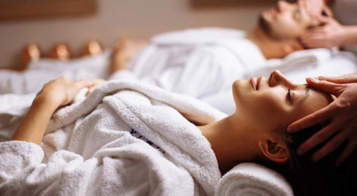 Photo of a woman and man in white robes, laying down relaxing at a spa (penny stocks)