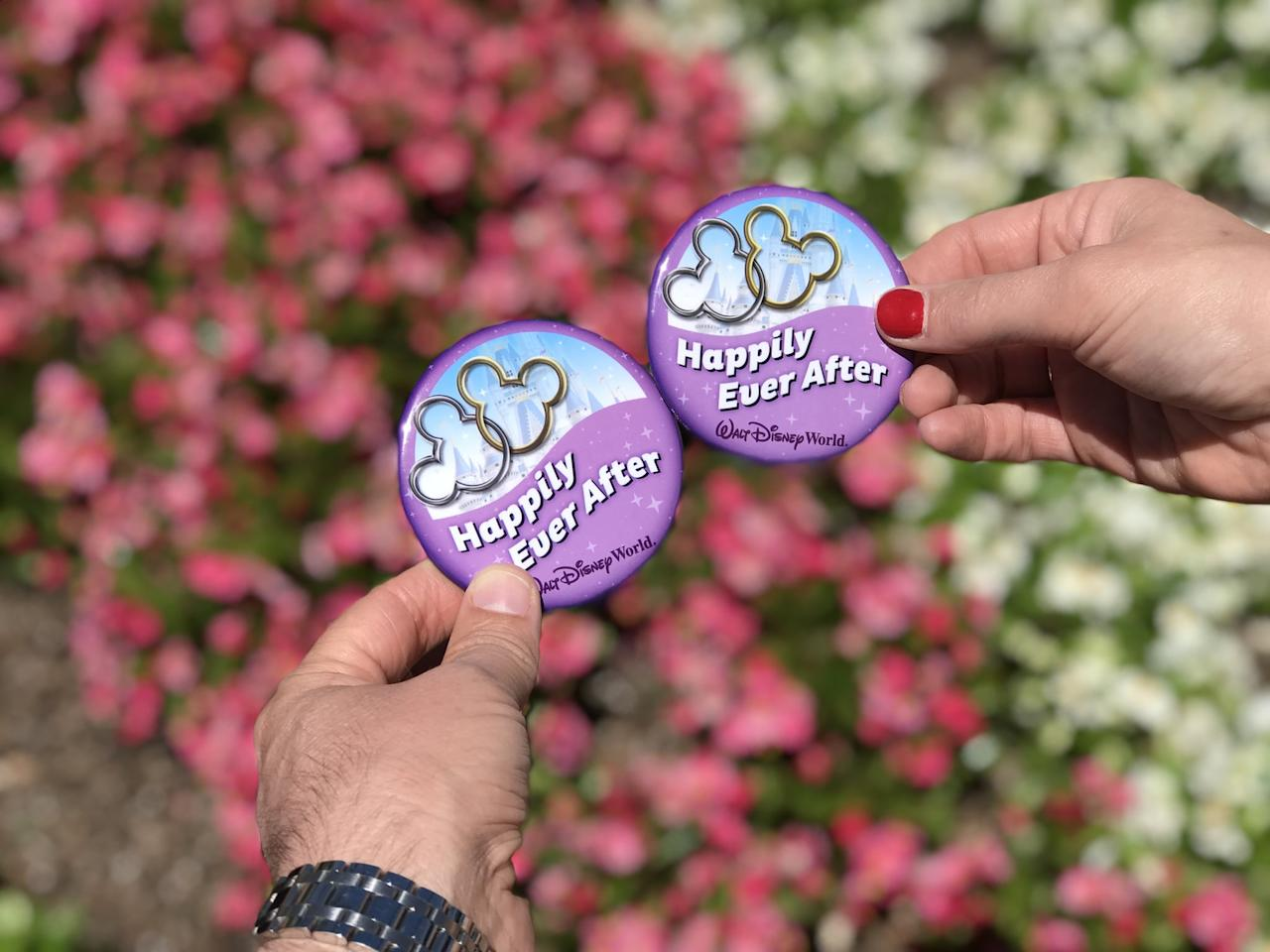 "<p>Disney offers an array of celebratory buttons to guests for free, but the ""Happily Ever After"" ones are the sweetest. In addition to being an adorable item for your outfits and vacation photos, the buttons will bring many ""Congratulations!"" from cast members are fellow parkgoers - and perhaps some fun extras (champagne or desserts at restaurants, for example) if they're feeling generous.</p>"