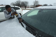 Mitra Bumphis, District Managet of KFC on West Main Street, cleans the base of his windshield to keep his wiper blades from freezing to the glass as he lets his car warm up at the West Main Street KFC early Monday morning in Tupelo. (Adam Robison/The Northeast Mississippi Daily Journal via AP)