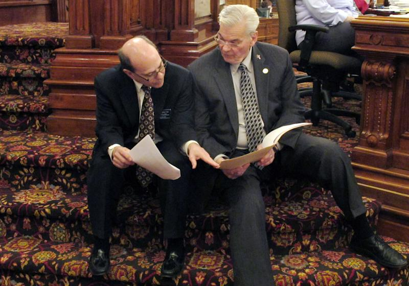 FILE - In this April 5, 2013, file photo Kansas state Reps. Steve Brunk, left, a Wichita Republican, and Arlen Siegfreid, right, an Olathe Republican, confer during a Statehouse debate in Topeka, Kan., prior to passage of the Second Amendment Protection Act. Kansas Gov. Sam Brownback signed the bill later and became the first to sign a measure threatening felony charges against federal agents who enforce certain firearms laws on guns made and owned in his state. (AP Photo/John Hanna)