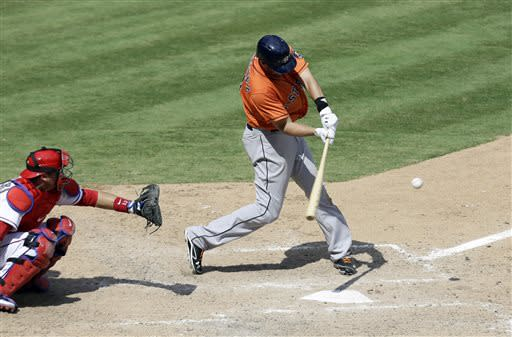Houston Astros' J.D. Martinez (14) connects for a single to center as Texas Rangers' A.J. Pierzynski watches in the seventh inning of a baseball game Sunday, July 7, 2013, in Arlington, Texas. (AP Photo/Tony Gutierrez)