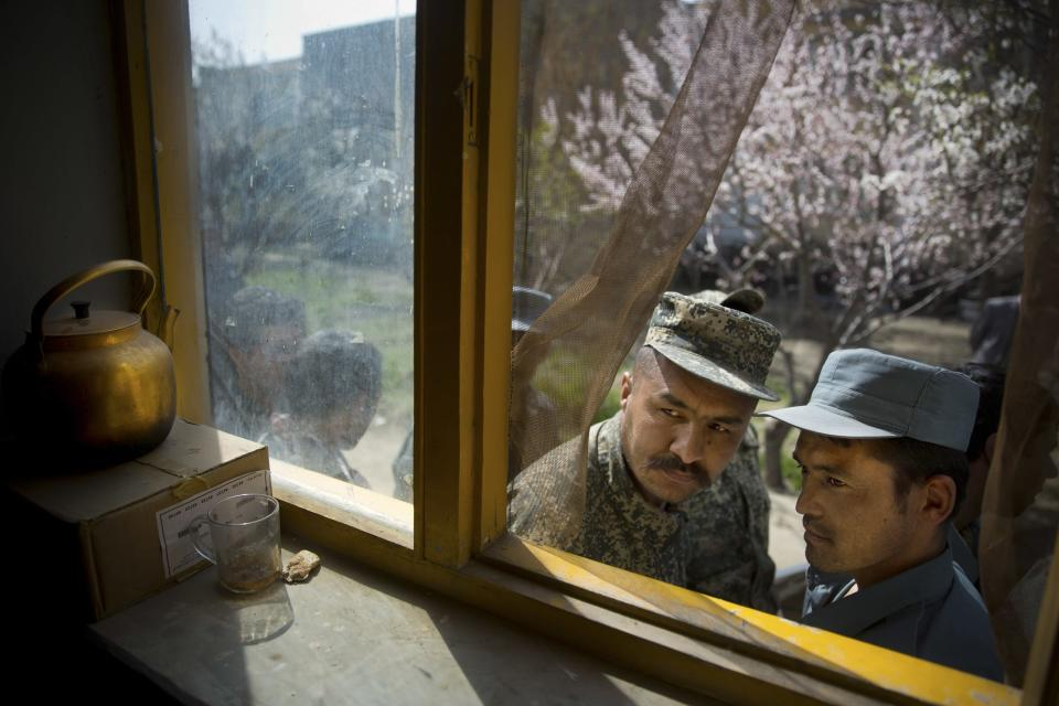 An Afghan soldier, left, and a police man peek through a window as they queue with others to get their registration card on the last day of voter registration for the upcoming presidential elections outside a school in Kabul, Afghanistan, Tuesday, April 1, 2014. (AP Photo/Anja Niedringhaus)