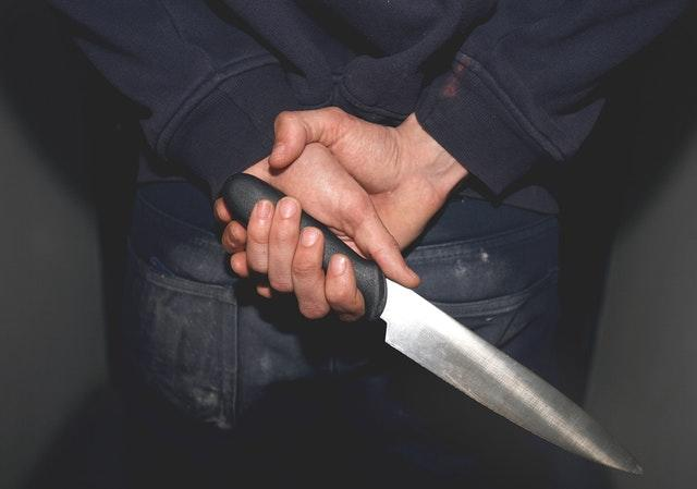 A man holding a knife behind his back