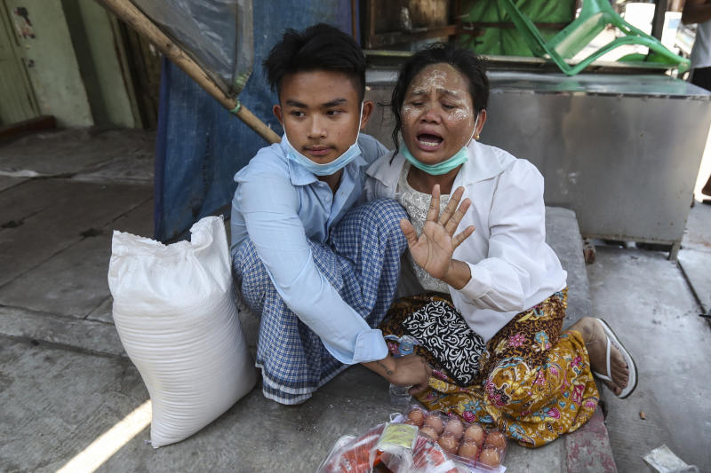A mother cries after her son, left, was released from Insein prison by a presidential pardon in Yangon, Myanmar, Friday, April 17, 2020. Myanmar says it is releasing almost 25,000 prisoners under a presidential amnesty marking this week's traditional Lunar New Year celebration. (AP Photo/Thein Zaw)