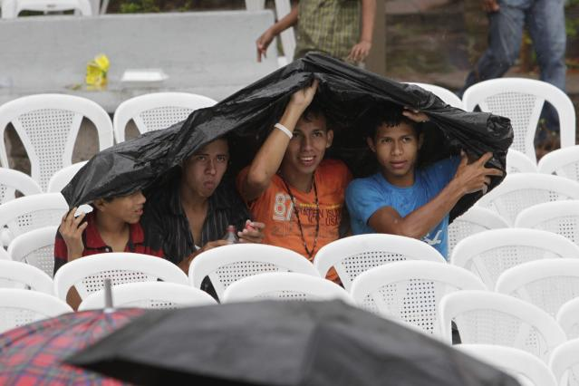 Honduran fans use a poncho to take cover from rain as they watch the 2014 World Cup soccer match against France broadcasted on a large screen in downtown Tegucigalpa June 15, 2014. REUTERS/Jorge Cabrera (HONDURAS - Tags: SPORT SOCCER WORLD CUP SOCIETY)