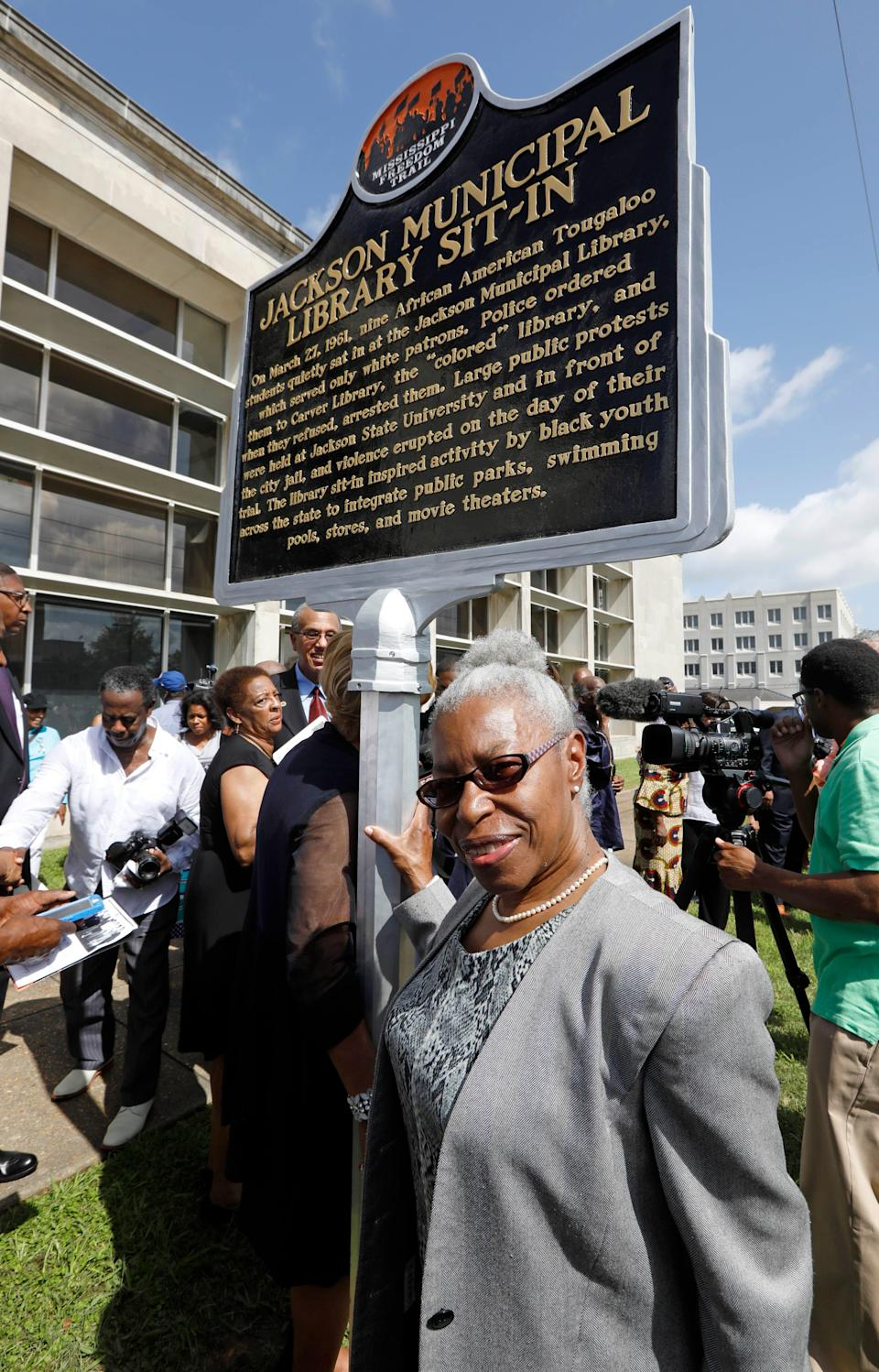 """Geraldine Edwards Hollis, a member of the """"Tougaloo Nine,"""" stands alongside the newest Mississippi Freedom Trail marker recognizing she and other Tougaloo College students for their peaceful sit-in in 1961 at the then whites-only Jackson Municipal Library, Thursday, Aug. 17, 2017. The library, sitting in the background, has served other purposes since the 1961 sit-in."""